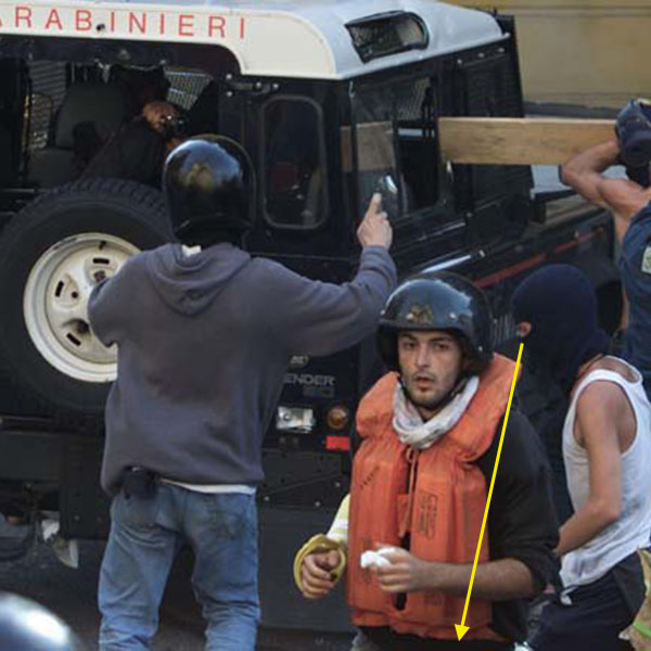 A CARABINIERE POINTS A GUN AS PROTESTERS ATTACK THEIR VEHICLE