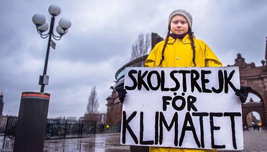 Foto3. Greta Thunberg, con il suo cartello e la famosa giacca a vento gialla, manifesta davanti alla sede del Parlamento svedese